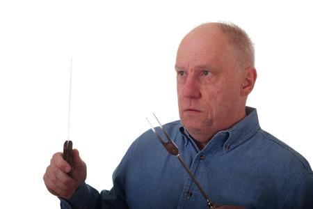 An older balding man in blue denim shirt holding carving knife and fork photo