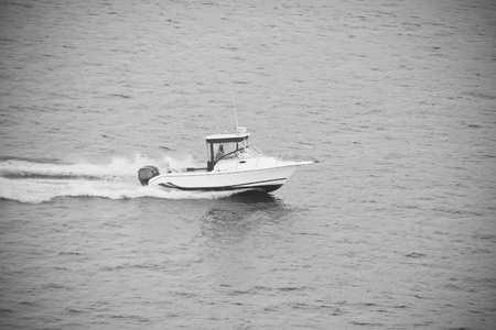 A white boat cruising across a lake in black and white Stock Photo - 11056076