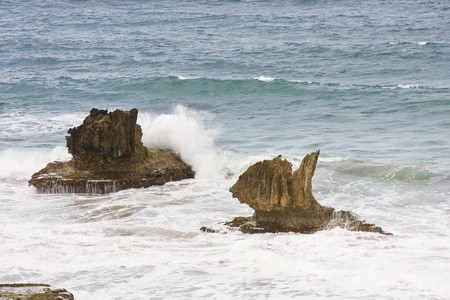 Ocean splashing against volcanic rocks lying in the surf Stock Photo - 11056079