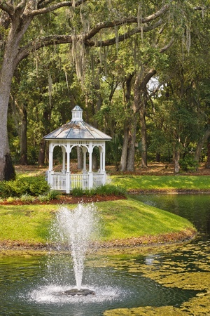 A white wood gazebo in the woods with a fountain in a lake