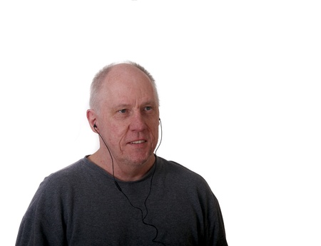 An older balding man listening to music on an MP3 player with ear buds photo