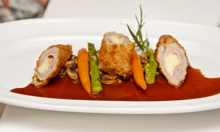 Veal Cordon Blue on White Plate with vegetables and gravy photo