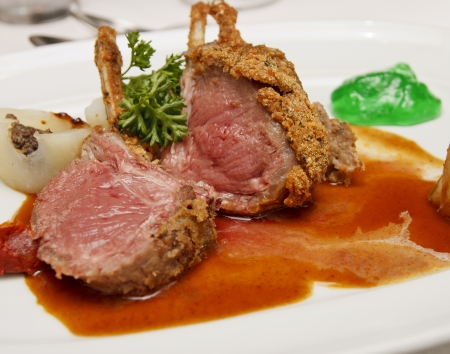 Lamb chops on a white plate with mint jelly
