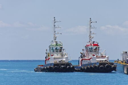 Two tugboats tied up at a calm harbor photo