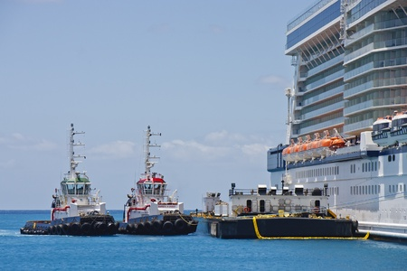 Two tugboats and a barge tied up to a cruise ship photo