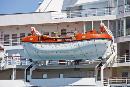 A large orange lifeboat harnessed to the side of a luxury cruise ship Stock Photo - 12382971
