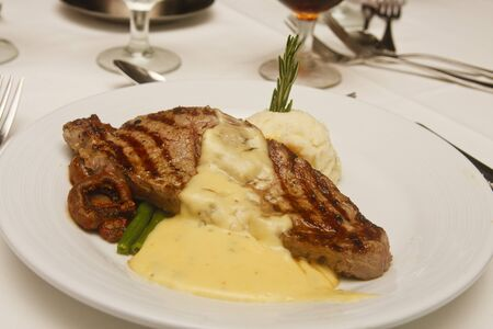 A grilled strip steak on a white plate with potatoes and bernaise sauce