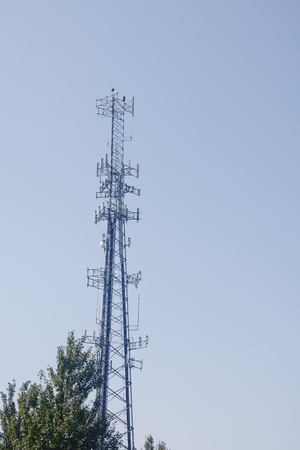 A cell phone tower against a clear blue sky Imagens