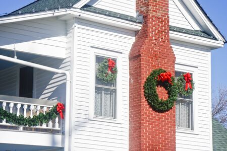A white classic two story wood house decorated for Chistmas photo