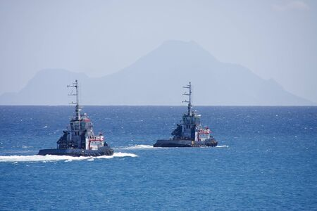 Two tugboats cruising out to open sea with hazy hills in the background photo