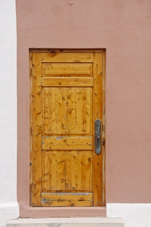 An old wooden door with a brass latch in a stucco wall Stock Photo - 12383022