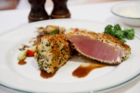 Seered and coated ahi tuna on a white plate with sauce