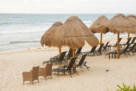 Rattan chairs and chaise lounges on a beach with straw thatch huts photo