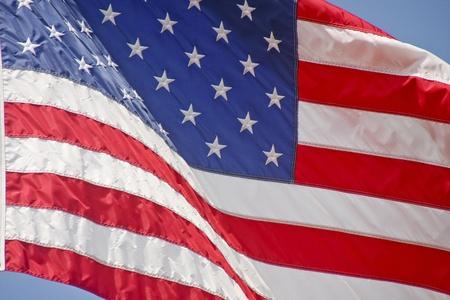 Een Amerikaanse vlag wapperen in de wind tegen een blauwe hemel