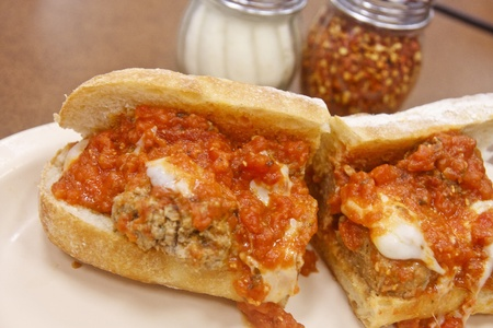 A classic meatball sub sandwich with parmesan cheese and hot pepper flakes in background Banque d'images