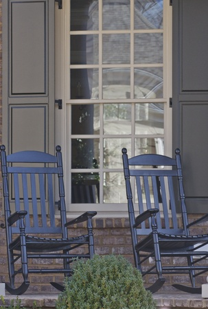 Two black rocking chairs on a residential porch photo