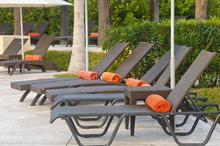 cabana: Row of brown chaise lounges on patio with orange beach towels