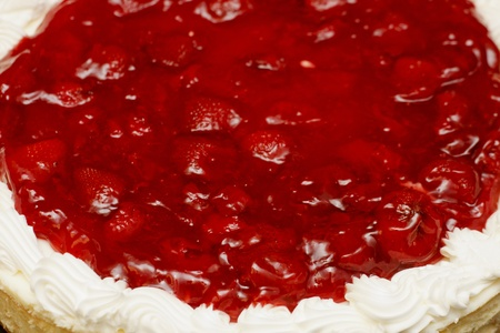 Strawberries and whipped cream on a whole cheesecake photo