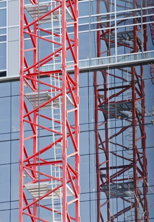 Red scaffolding on construction crane reflected in windows photo