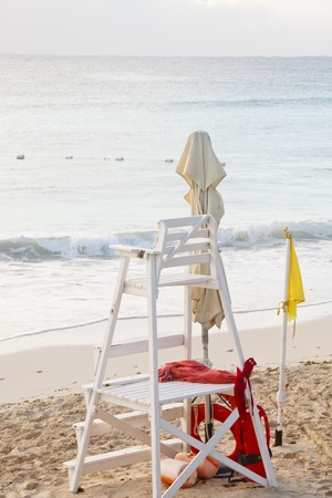 A white wood lifeguard stand with a yellow caution flag Stock Photo - 13059030