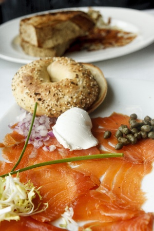 A platter of smoked salmon with a toasted everything bagel garnished with red onion, scallion, cream cheese and capers Stock Photo - 13310843
