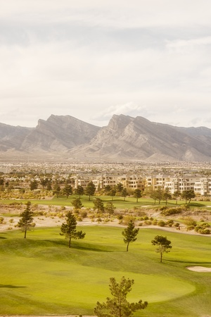 condominium complex: A desert condominium complex on a golf course with mountains in background
