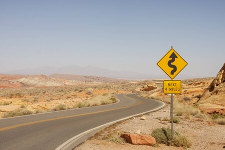 A road sign in the middle of a desert showing curves ahead photo
