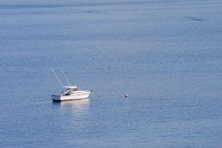 Un barco de pesca de bonito blanco anclado en una bahía azul con el pelícano en la proa Foto de archivo - 13483048
