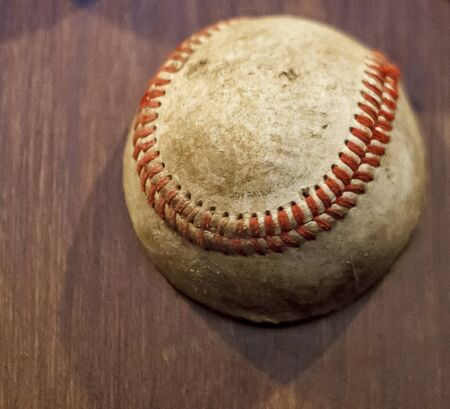 A very old, dirty and worn baseball on a wood shelf