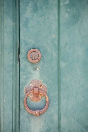 Old brass lock and knocker on a green door