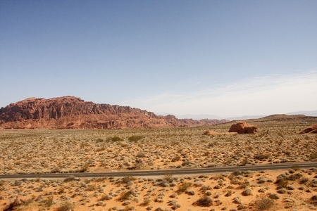 A two lane highway across the desert with rocks in distance Stock Photo - 13528925