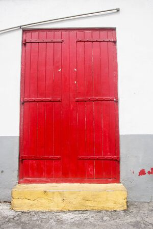 white trim: An old red door over yellow curb in a white and gray wall