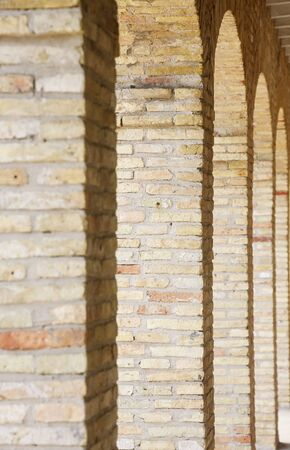 distance: Rows of old yellow brick arches into distance Stock Photo