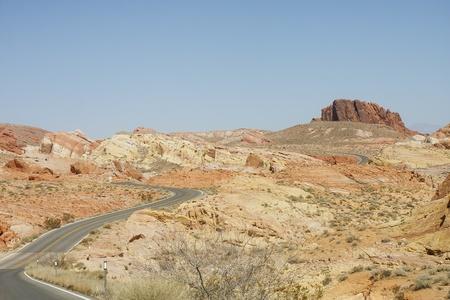 A two lane road winding through the desert near red rocks photo