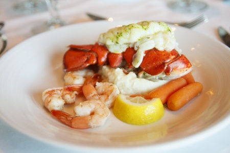 lobster tail: A plate of lobster tail and shrimp on a white plate with lemon wedge and carrots