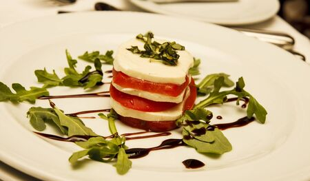 A caprese salad of fresh sliced tomatoes and mozzarella cheese stacked on a white plate garnished with arugula and drizzled with balsamic vinegar Imagens