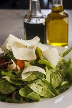 An arugula salad with shaved parmesan cheese with oil and vinegar in background Imagens