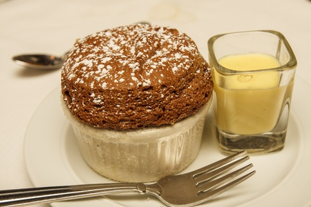 A fresh baked chocolate souffle on a plate with vanilla sauce and a fork Stock Photo