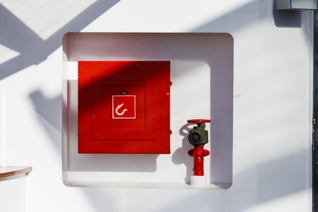 Red firebox and hose connection on white ships bulkhead photo