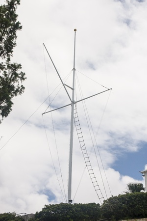 A ships mast with ladder under clouds on Bermuda
