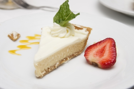 A slice of key lime pie on a plate garnished with a strawberry and mint leaf