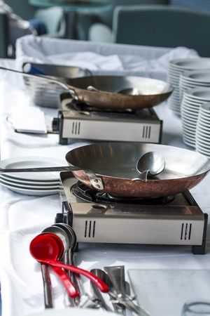 Saute pans on portable burners at buffet ready to cook omelets and crepes