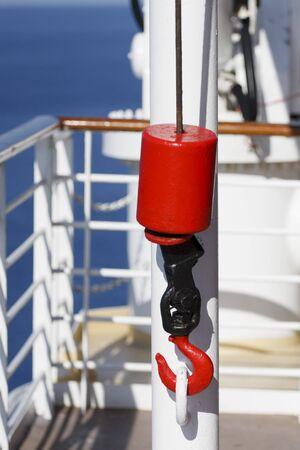 polea: Un gancho de metal rojo y negro sobre la polea de cable