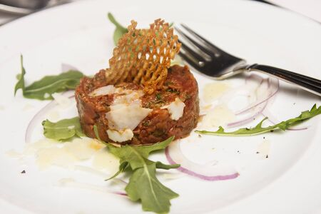 Steak  tartar garnished with potato and arugula on white plate with a fork