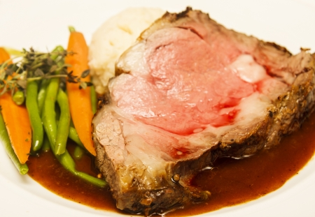 Rare slab of prime rib beef on a plate with au jus, carrots, and beans, garnished with rosemary