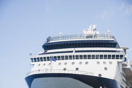 ship bow: Bow of blue and white luxury cruise ship under blue skies