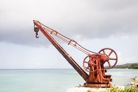 crank: Una vieja gr�a oxidada, color rojo con manivela manual en la orilla de una isla tropical