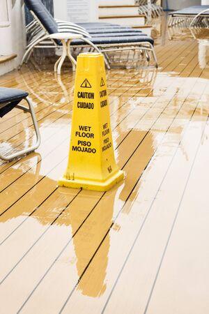 wet floor: Warning Cone on wet wooden ships deck Editorial