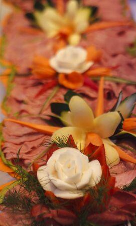 carnes y verduras: Carnes en rodajas sobre un buffet decorado con verduras talladas