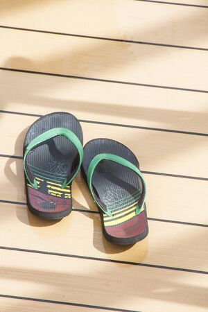 sandels: Pair of colorful rubber sandals on a wood deck